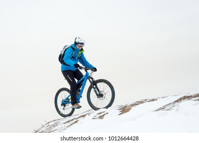 Cyclist in Blue Riding the Mountain Bike on the Rocky Winter Hill Covered with Snow. Extreme Sport and Enduro Biking Concept.