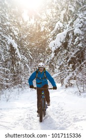 Cyclist in Blue Riding the Mountain Bike in the Beautiful Winter Forest Lit by the Sun and Covered with Snow. Extreme Sport and Enduro Biking Concept.
