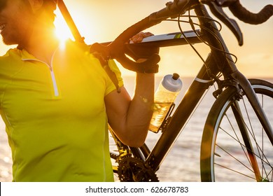 Cyclist carrying road bike at sunset after long day of biking activity riding outdoors. Healthy man living an active lifestyle cycling doing outdoor sports.