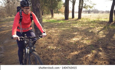 Cyclist. Caucasian sport woman rides along the track in the forest on a spring sunny day. Riding a sportsman girl on a mountain bike on a rural trail in nature. Outdoor sports.