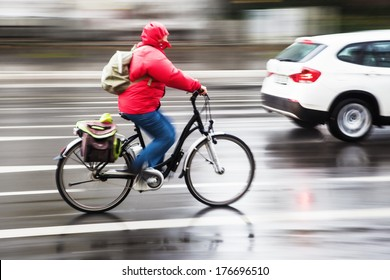 cyclist in the city traffic at a day with heavy rain