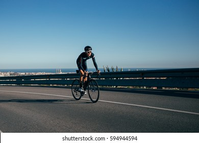 Cyclist climbing up a mountain road with city below low sunlight and shadow