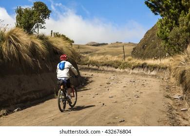 Cyclist climbing mountain road in Ecuadorian Andes