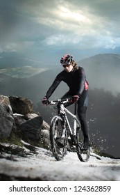 Cyclist climbing on a rock