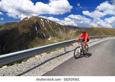 Cyclist climbs hard a mountain road in summer