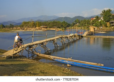 Cyclist crossing rickety wooden bridge in Vang Vieng, Laos.