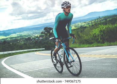 Cyclist is cycling, climbing up to the top.