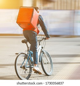 Cyclist delivering food. Courier on bike with thermal backpack, food delivery. Fast delivery of food by bicycle