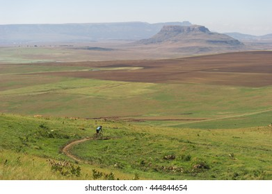 Cyclist descending down a hill in beautiful nature with amazing hills behind it.