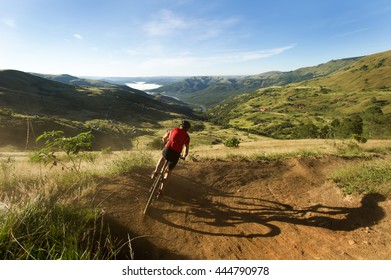Cyclist descending into a beautiful green valley on a dirt track.