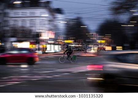 A cyclist drives at twilight over a road intersection