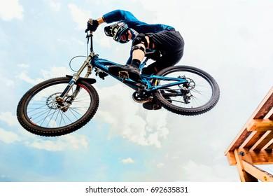cyclist drops on jump downhill mountain biking