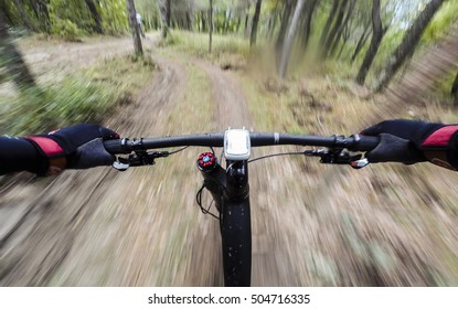 Cyclist during a mountain bike race in a forest. Drop of water on lens. POV