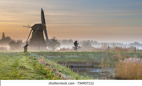 Cyclist in foggy early morning landscape with historic wooden windmill