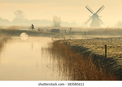 Cyclist and a foggy, spring sunrise in the Dutch countryside.