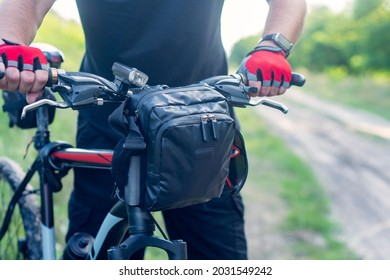 A cyclist in gloves near a mountain bike with a bag on the handlebars