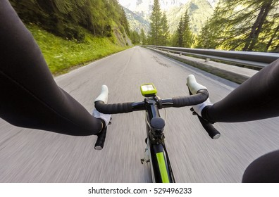 Cyclist Going dowun on mountainous road. Cycling in Dolomites, Passo Falzarego. POV Original point of view