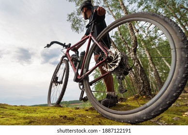 Cyclist with a gravel bike enjoying the beautiful scenery while relaxing after training. Low angle view.