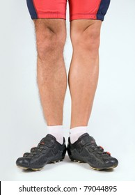 Cyclist with a half-shaven legs. Male legs in cycling pants and shoes. Cyclists shave their legs.