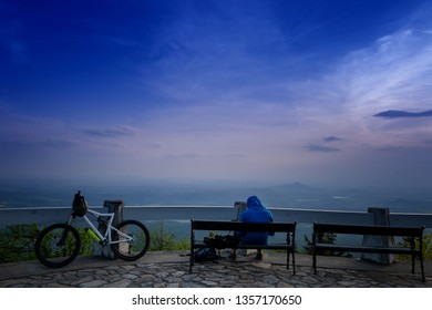 Cyclist having a relax on top of a mountain with bike on a end of a day