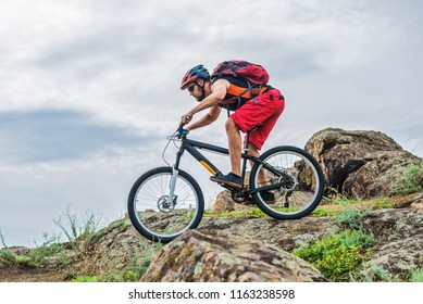 Cyclist in a helmet and with a backpack riding down the rock on a mountain bike, an active lifestyle. Concept of extreme cycling, enduro, mtb.