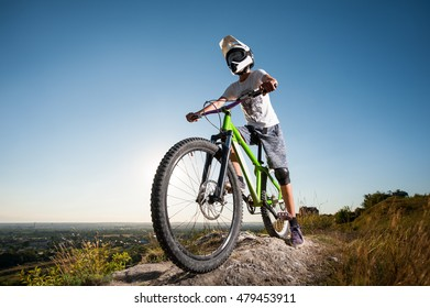 Cyclist in helmet and glasses stay on the mountain bicycle at the hill under blue sky against blue sky and looking into the distance. Wide angle view
