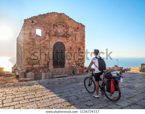 Cyclist with his bicycle touring in front of the Temple of Hercules in San Marco d'Alunzio, Sicily, Italy.