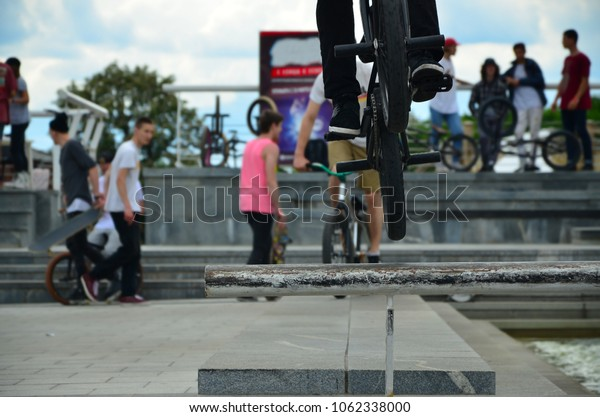 A cyclist jumps over a pipe on a BMX bike. A lot of people with bicycles in the background. Extreme sports concept