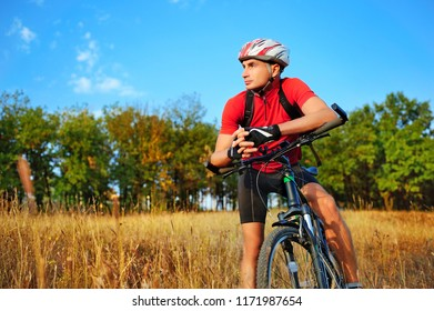 Cyclist leaning at the bicycle looking to the side