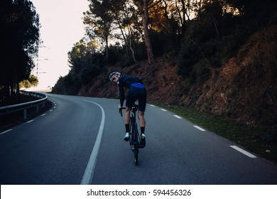 Cyclist looking back at the camera while climbing a dark mountain road