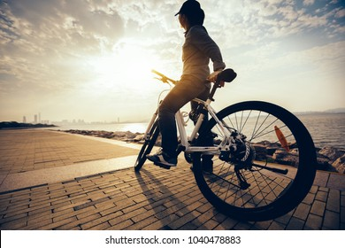 cyclist looking at the sunrise while riding bike in the sunrise coast path