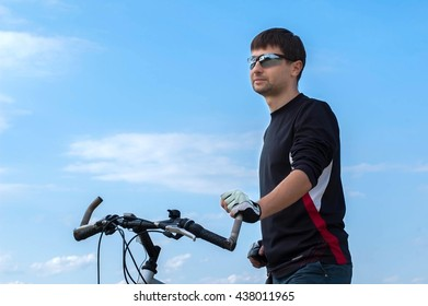 Cyclist looks away, holds the handlebar and stands against the sky.