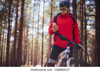 A cyclist looks into the smartphone on the background and forest.