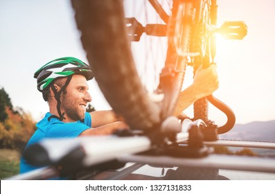 Cyclist man hold his bike on the car roof
