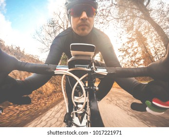 Cyclist man portrait on sunset. Young man with helmet and sunglasses on road bike. POV Original Point of View