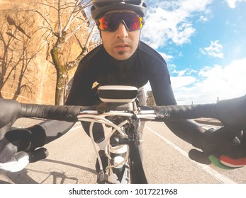 Cyclist man portrait. Young man with helmet and sunglasses on road bike. POV Original Point of View