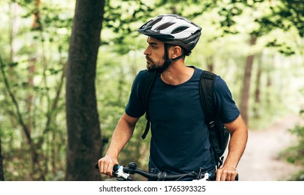 Cyclist man riding bike in the mountain. Athelete male in cycling gear practising outside on nature background. Travel and extreme sport concept.