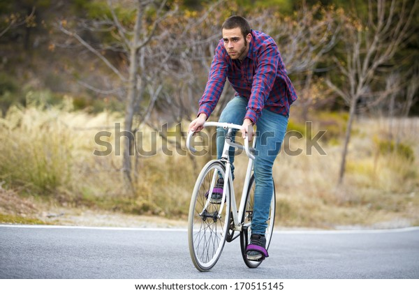 Cyclist man riding fixed gear sport bike in sunny day on a mountain road