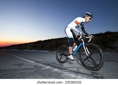 Cyclist man riding mountain bike at sunset on a mountain road