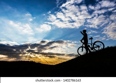 Cyclist man silhouette on mountain bike on the road.
