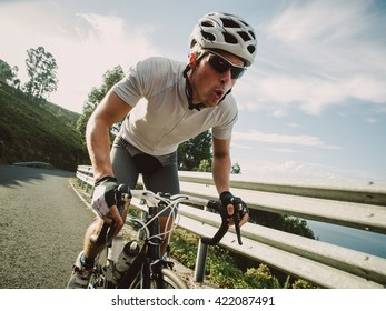 Cyclist in maximum effort pedaling outdoors in a sunny day
