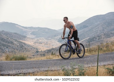 Cyclist in maximum effort ride his bicycle on mountain road.