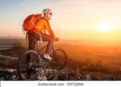 Cyclist with mountain bike on top observing the view. At sunset with lens flare