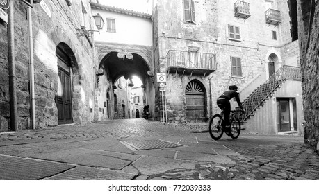 Cyclist in old street of historical town in Italy.