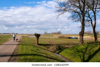 Cyclist on a bicycle path along the river Linde near Kuinre in the Dutch province Overijssel