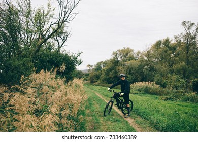 a cyclist on black bicycle travels through the countryside