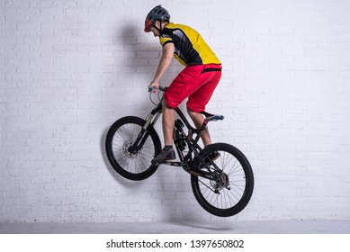 Cyclist on a full mountain suspension performing a jump against the background of a brick wall. Cycling, active lifestyle.