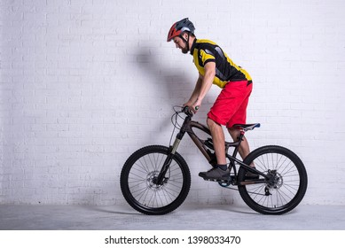 Cyclist on a full mountain suspension against a brick wall. Cycling, active lifestyle.
