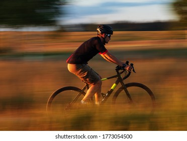 Cyclist on a gravel bike in a field at sunset. Motion blur effect. Travel and active lifestyle concept.