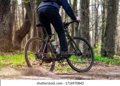 Cyclist on a gravel bike. A cyclist rides along a forest path drifting with the rear wheel and raising the pitch. Active sport concept.